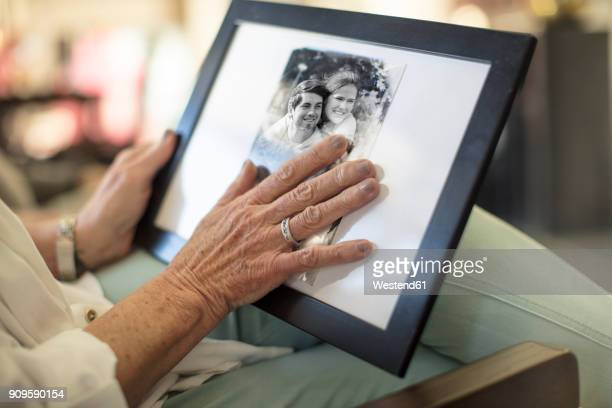 close-up of senior woman holding a photograph - photograph stock pictures, royalty-free photos & images