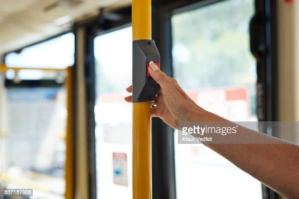 Close-up of senior woman pushing 'stop' button inside public bus