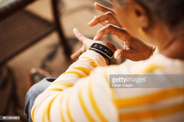 close-up of senior woman using smart watch - wearable computer stock pictures, royalty-free photos & images
