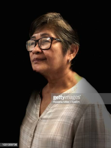 close-up of senior woman wearing eyeglasses against black background - rowena miller stock photos and pictures