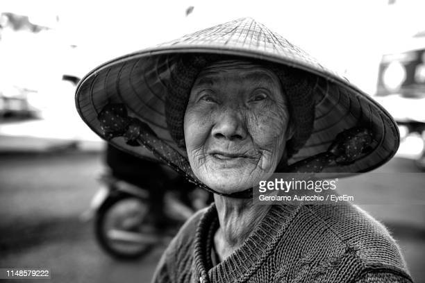 close-up of senior woman wearing hat making face - old man funny face black and white stock photos and pictures