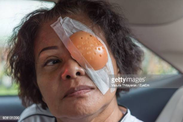 close-up of senior woman with bandage on eye in car - eye injury stock pictures, royalty-free photos & images