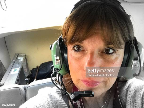 Close-Up Of Senior Woman With Headphones In Airplane