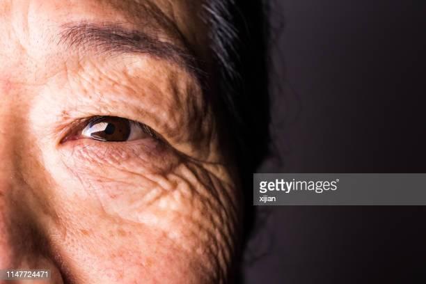 close-up do olho da mulher sênior - perto de - fotografias e filmes do acervo