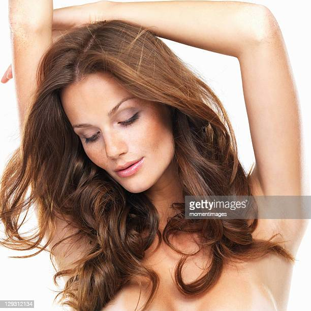 Close-up of sensuous woman with hands over head