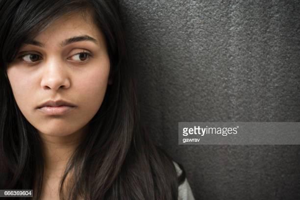 Close-up of serene Asian girl thinking.