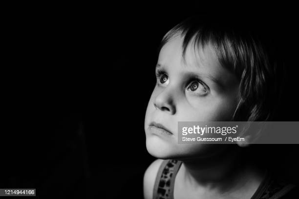close-up of serious boy looking up against black background - steve guessoum stockfoto's en -beelden