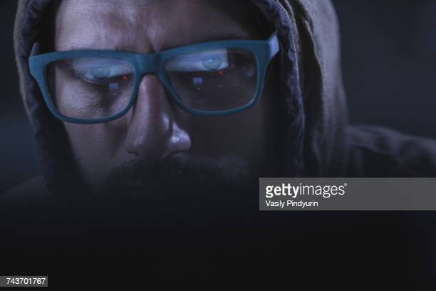 close-up of serious computer hacker wearing eyeglasses and hood - con man stock photos and pictures