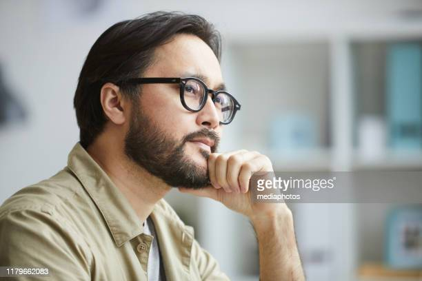 close-up of serious creative young asian man with beard being deep in thoughts while working on project in office - hand on chin stock pictures, royalty-free photos & images