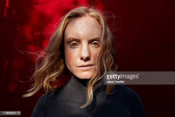 close-up of serious woman standing against red wall - serious stock pictures, royalty-free photos & images
