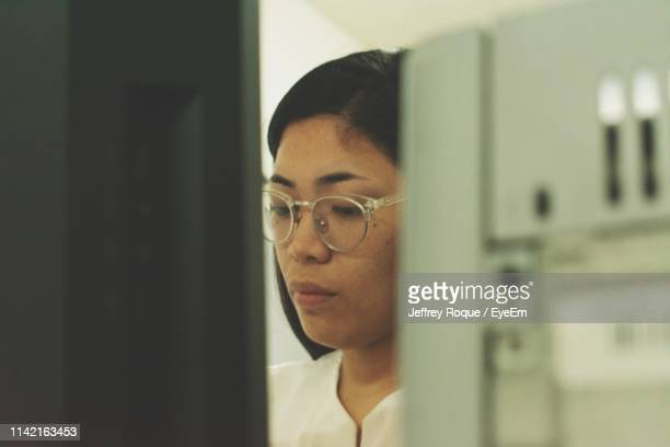 close-up of serious young woman working in office - jeffrey roque stock photos and pictures