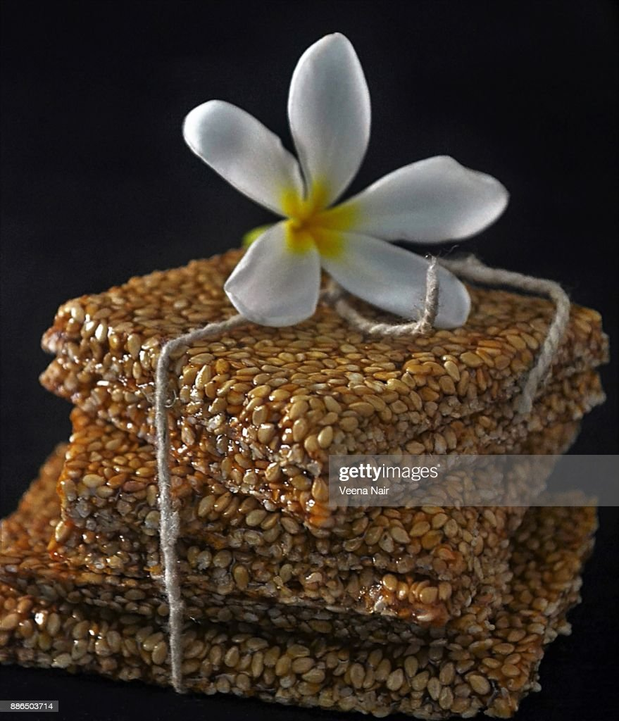 Close-up of sesame brittle/chikki and frangipani flower : Stock Photo