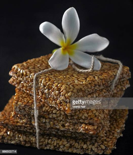Close-up of sesame brittle/chikki and frangipani flower