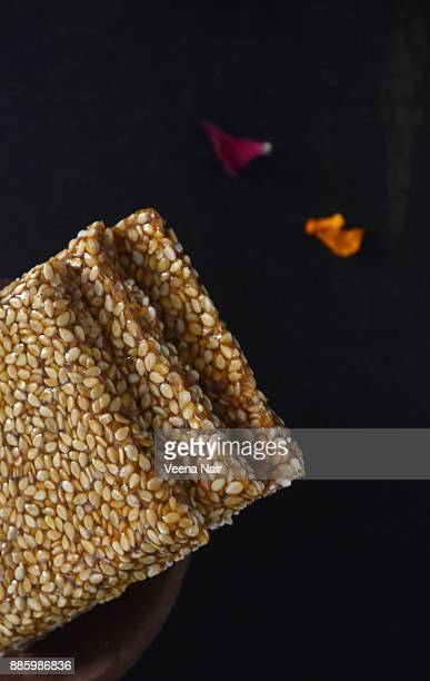 close-up of sesame brittle/chikki in a clay bowl-indian snack - makar sankranti stock pictures, royalty-free photos & images