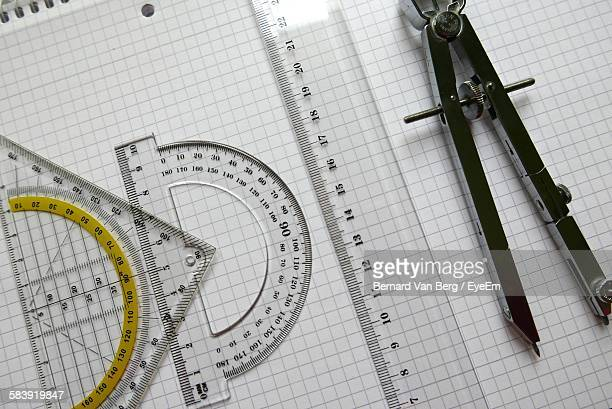 Close-Up Of Set Square And Protractor With Drawing Compass By Ruler On Book