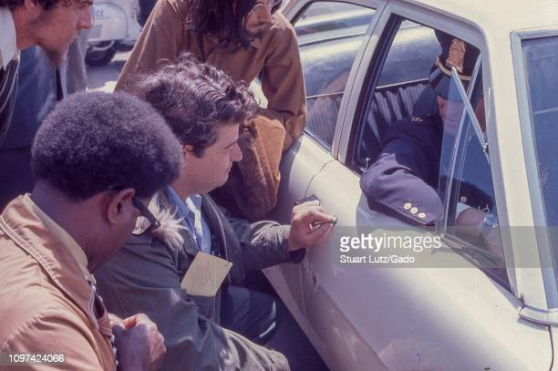 Closeup of several men in profile bending to speak with a police officer sitting in a car during demonstrations related to the Vietnam War May Day...