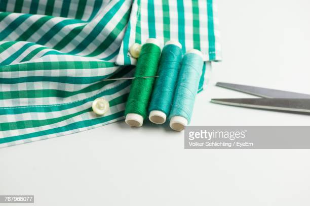 close-up of sewing item with shirt on white background - button sewing item stock pictures, royalty-free photos & images