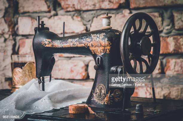 close-up of sewing machine against brick wall - sewing machine stock pictures, royalty-free photos & images
