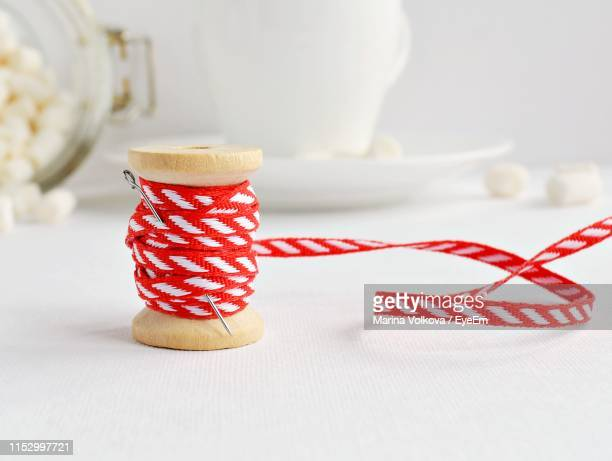 close-up of sewing needle and ribbon on table - marina weisband stock-fotos und bilder