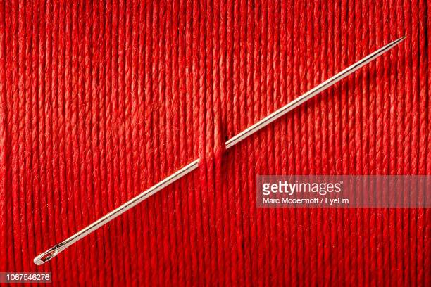 close-up of sewing needle in red thread - sewing needle stock pictures, royalty-free photos & images