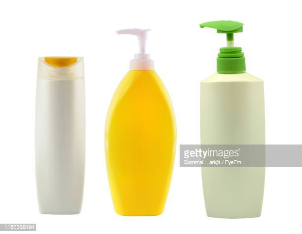 close-up of shampoo bottles against white background - shampoo stock pictures, royalty-free photos & images
