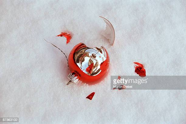 Close-up of shattered Christmas decoration in snow