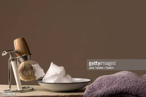 Close-Up Of Shaving Equipment And Towel On Table Against Colored Background