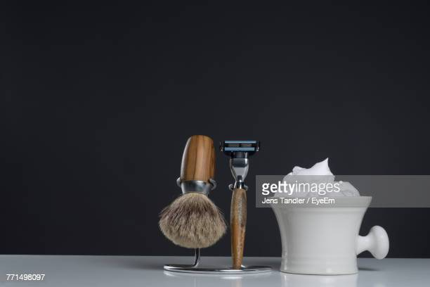 Close-Up Of Shaving Equipment On Table Against Black Background