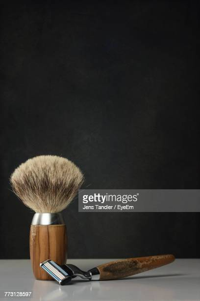 close-up of shaving equipment on table against black background - shaving brush stock photos and pictures