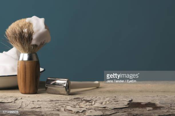 close-up of shaving equipment on table against blue background - razor stock photos and pictures