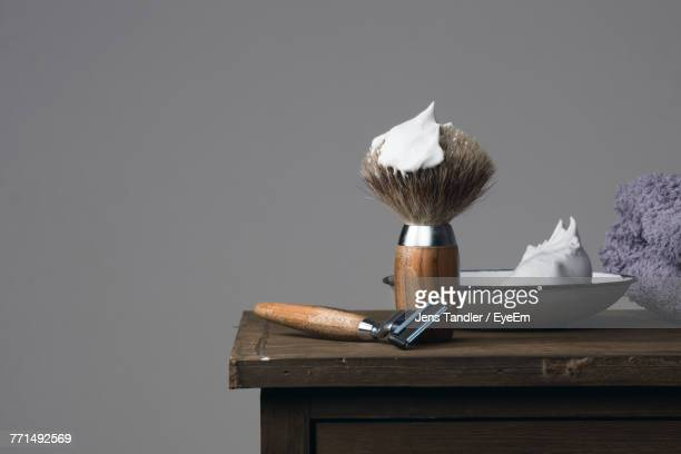 close-up of shaving equipment on table against gray background - shaving brush stock photos and pictures