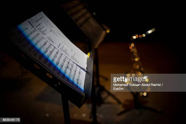 Close-Up Of Sheet Music On Stand In Dark Room
