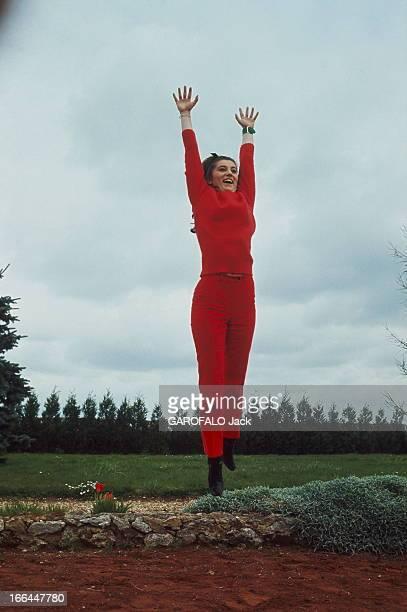 CloseUp Of Sheila Attitude souriante de SHEILA toute de rouge vêtue sautant en l'air les bras audessus de la tête dans le jardin de la maison de...