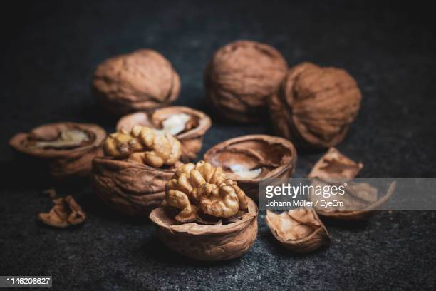 close-up of shells on table against black background - walnut stock pictures, royalty-free photos & images