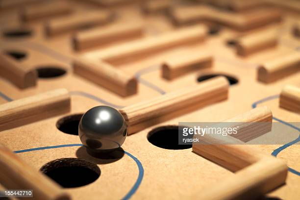 closeup of shiny metal ball navigating a labyrinth maze - obstacle course stock photos and pictures