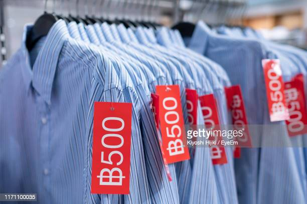 close-up of shirt with price tag hanging in store - price tag stock pictures, royalty-free photos & images