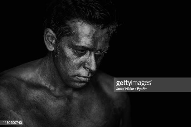 close-up of shirtless man with face paint against black background - body paint fotografías e imágenes de stock