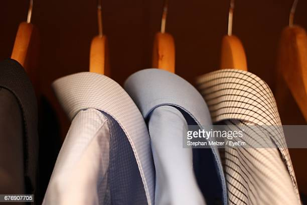 close-up of shirts hanging in wardrobe - clothes rack stock pictures, royalty-free photos & images