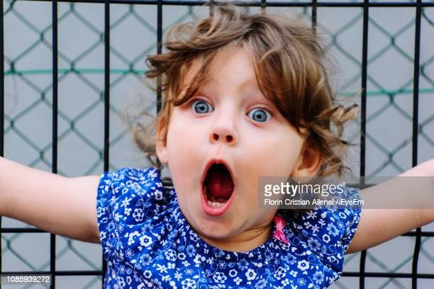 close-up of shocked girl with mouth open against fence - surprise face kid - fotografias e filmes do acervo