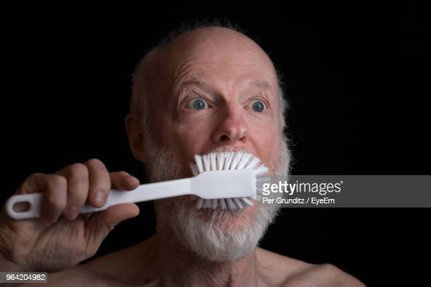 Close-Up Of Shocked Man Brushing Teeth Over Black Background