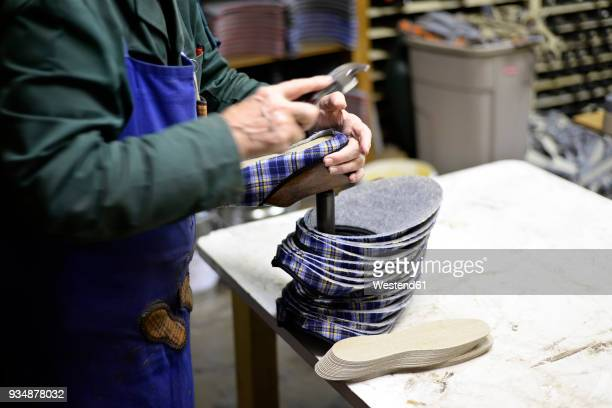 close-up of shoemaker working on slippers in workshop - shoe factory stock pictures, royalty-free photos & images