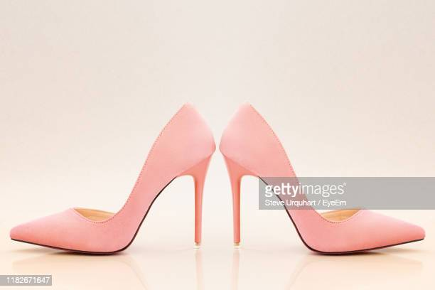 close-up of shoes against beige background - stiletto stock pictures, royalty-free photos & images