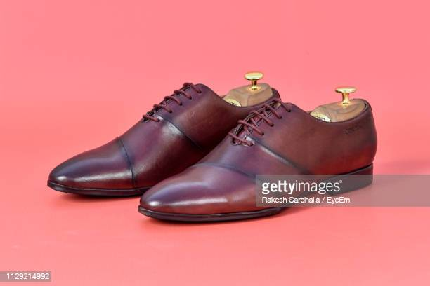 close-up of shoes against coral background - leather shoe stock pictures, royalty-free photos & images