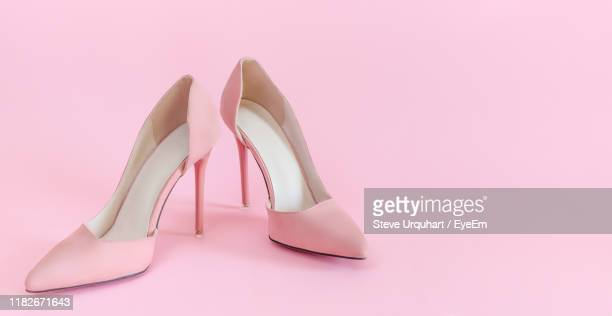 close-up of shoes against pink background - talons hauts photos et images de collection