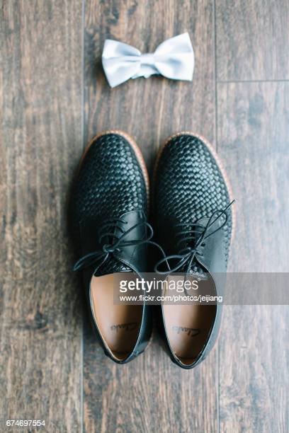 Close-Up Of Shoes And Bow Tie On floor