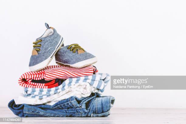close-up of shoes and clothes on table against white background - womenswear stock pictures, royalty-free photos & images