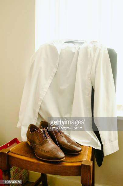 close-up of shoes and shirt on chair at home - menswear photos et images de collection