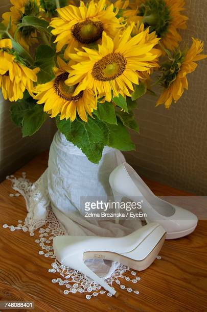 Close-Up Of Shoes By Sunflowers In Vase On Table