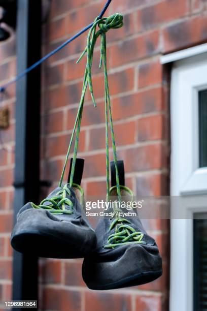 close-up of shoes hanging on wall - sheffield stock pictures, royalty-free photos & images