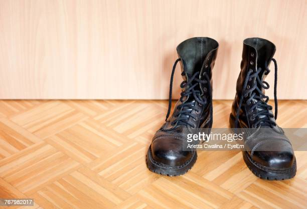 close-up of shoes on hardwood floor - black boot stock pictures, royalty-free photos & images